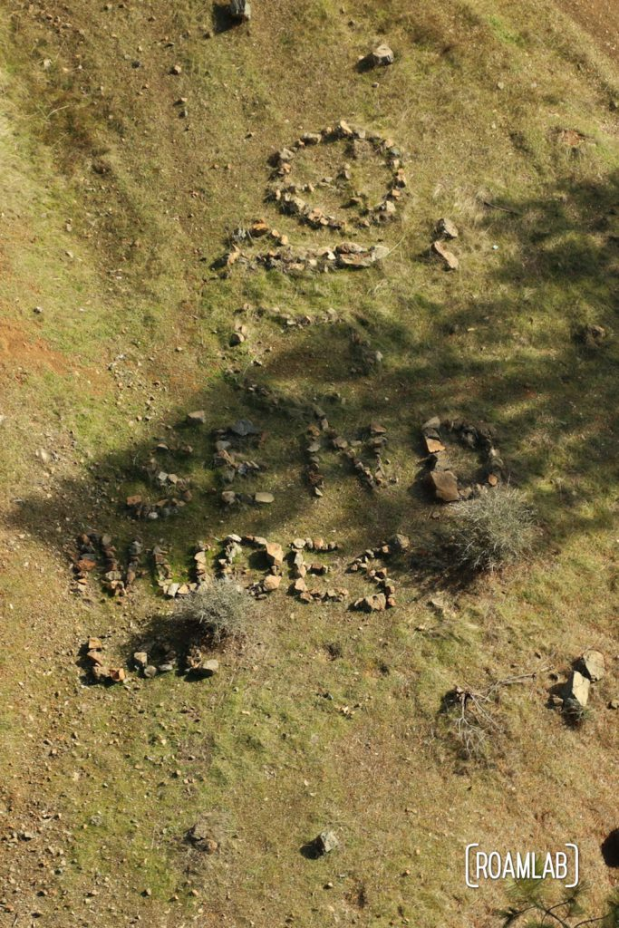 """Rocks arranged on the ground to spell """"SEND NUDES"""" from the air."""