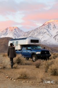 Man walking toward a 1970 Avion C11 truck camper with the pink tipped Sierra Nevada at dawn.