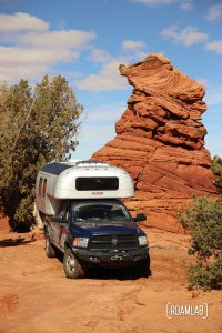 1970 Avion C11 truck camper parked next to a red rock hoodoo in Vermillion Hills National Monument.