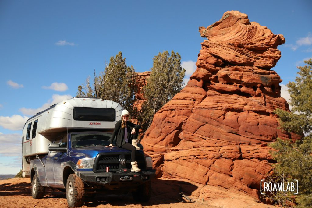 Woman sitting on a 1970 Avion C11 truck camper parked next to a red rock hoodoo in Vermillion Hills National Monument.