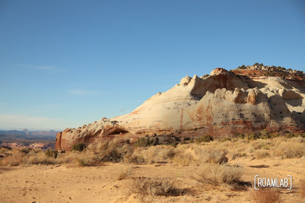 Pinkish white rock formation surrounded by sand in White Pocket.