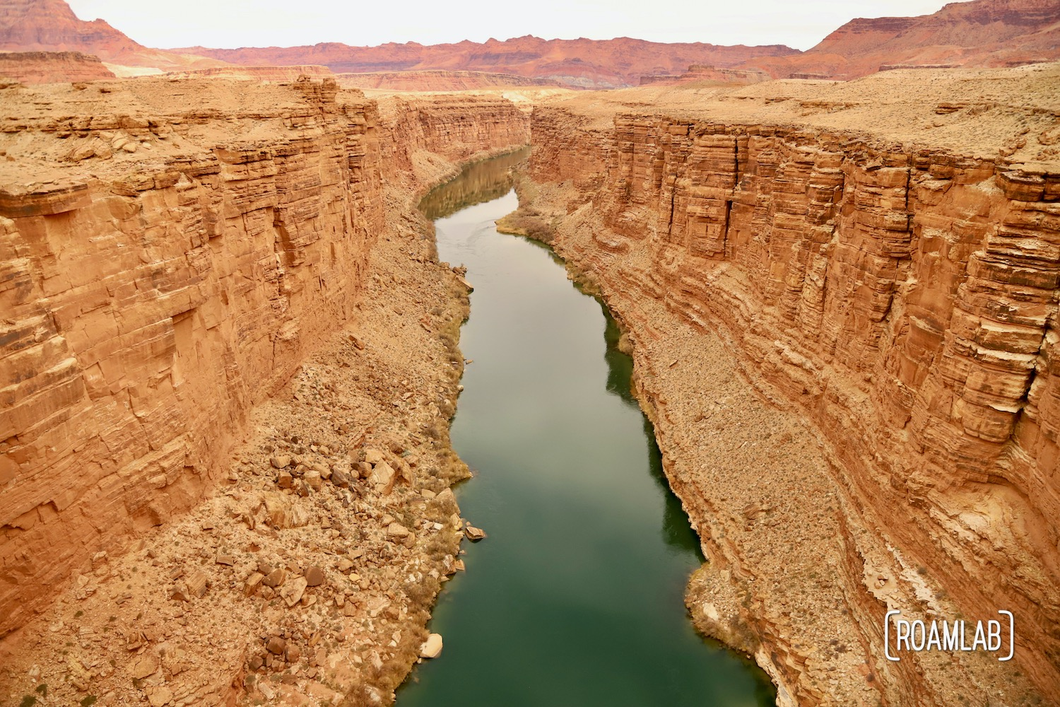 The wide Colorado River flowing between the golden cliffs of the Marble Canyon.