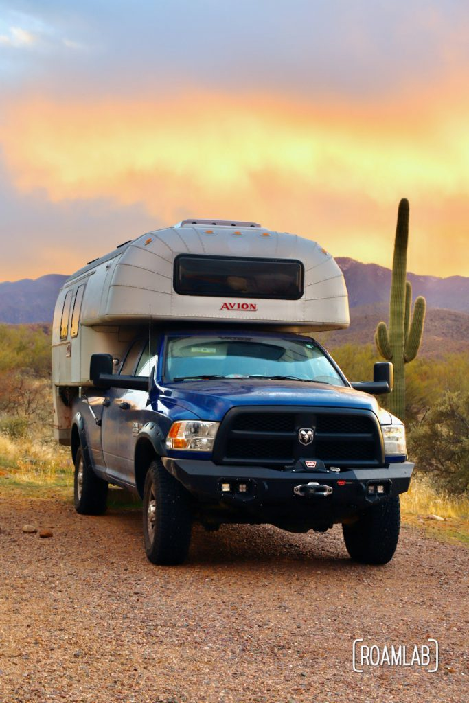 A brilliant sunset lighting up the background with a 1970 Avion C11 truck camper parked at Cholla Campground.