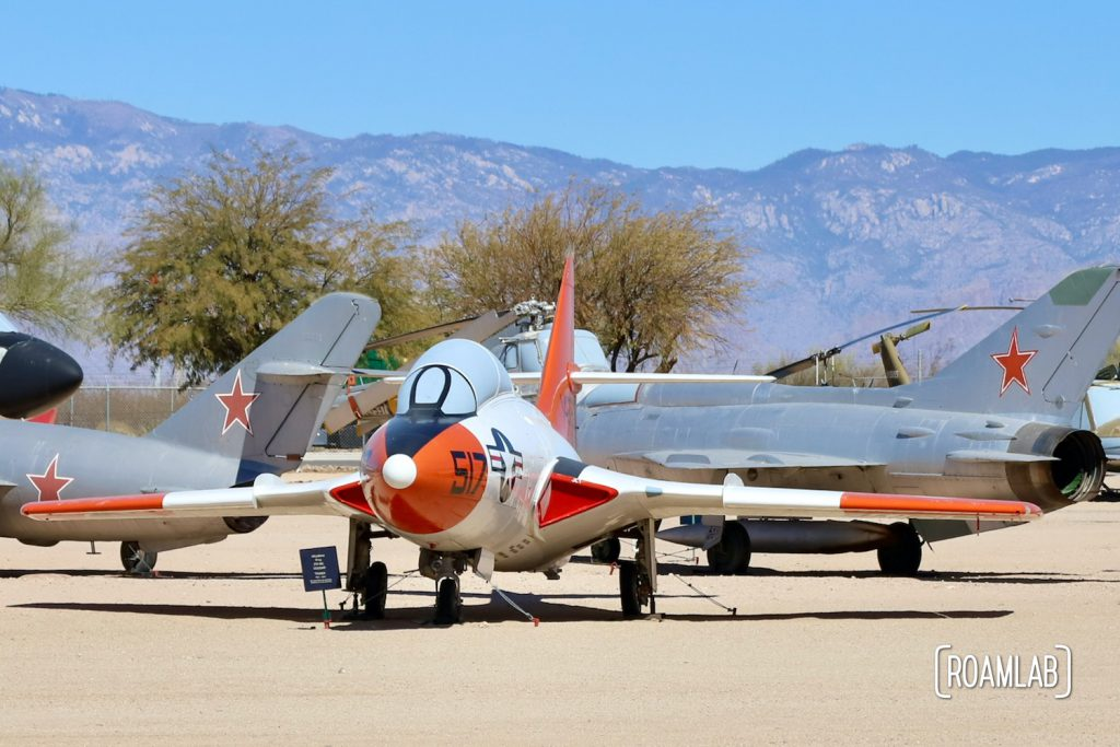 Colorful fighter planes scattered across the outdoor exhibits of the Pima Air & Space Museum.