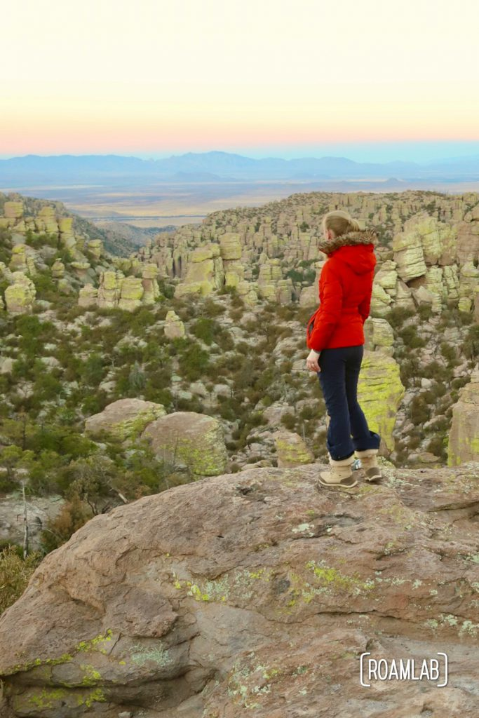 Woman looking down into a valley of hoodoos with mountains in the background on Echo Canyon Loop Trail at Chiricahua National Monument Arizona