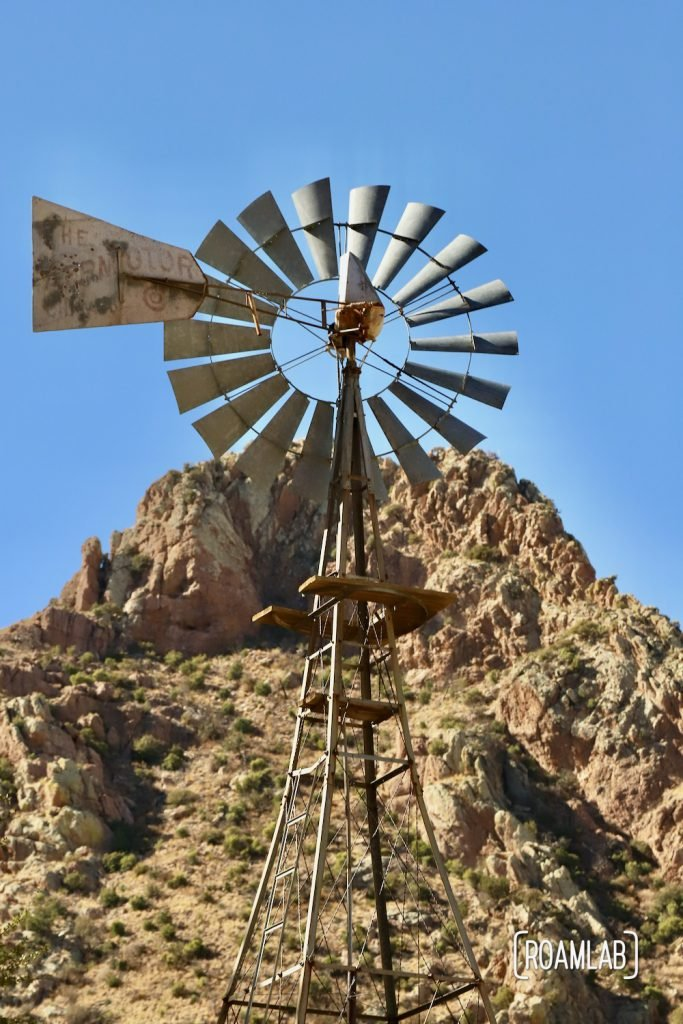 Faraway Ranch windmill with rocky hilltop in the background along the Silver Spur Meadow Trail in Chiricahua National Monument Arizona.