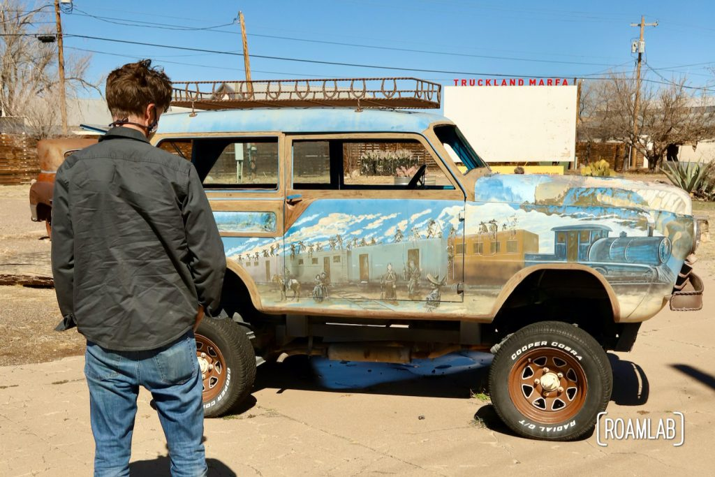 Man standing in front of a mural painted on the side of an old car with a sign for Truckland Marfa in the background.