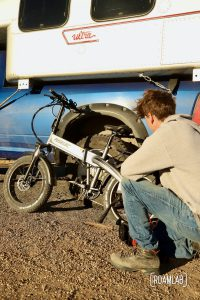 Man crouching in front of a bicycle resting on an 1970 Avion C11 truck camper.