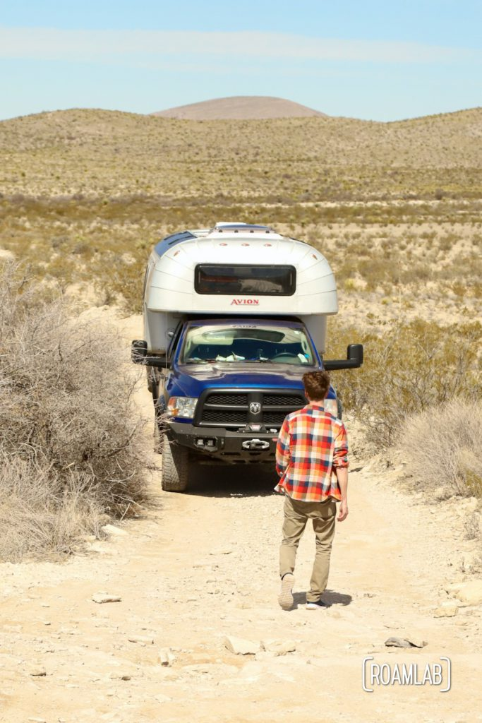 Man in a plaid shirt inspecting a rocky dirt road in front of a dusty 1970 Avion C11 truck camper along Old Ore Road in Big Bend National Park, Texas.