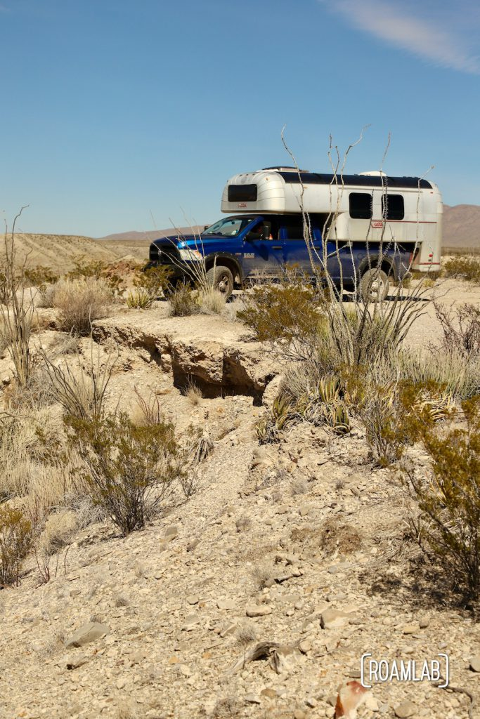 Aluminum 1970 Avion C11 truck camper on a blue truck on an overlook surrounded by desert plants along Old Ore Road in Big Bend National Park, Texas