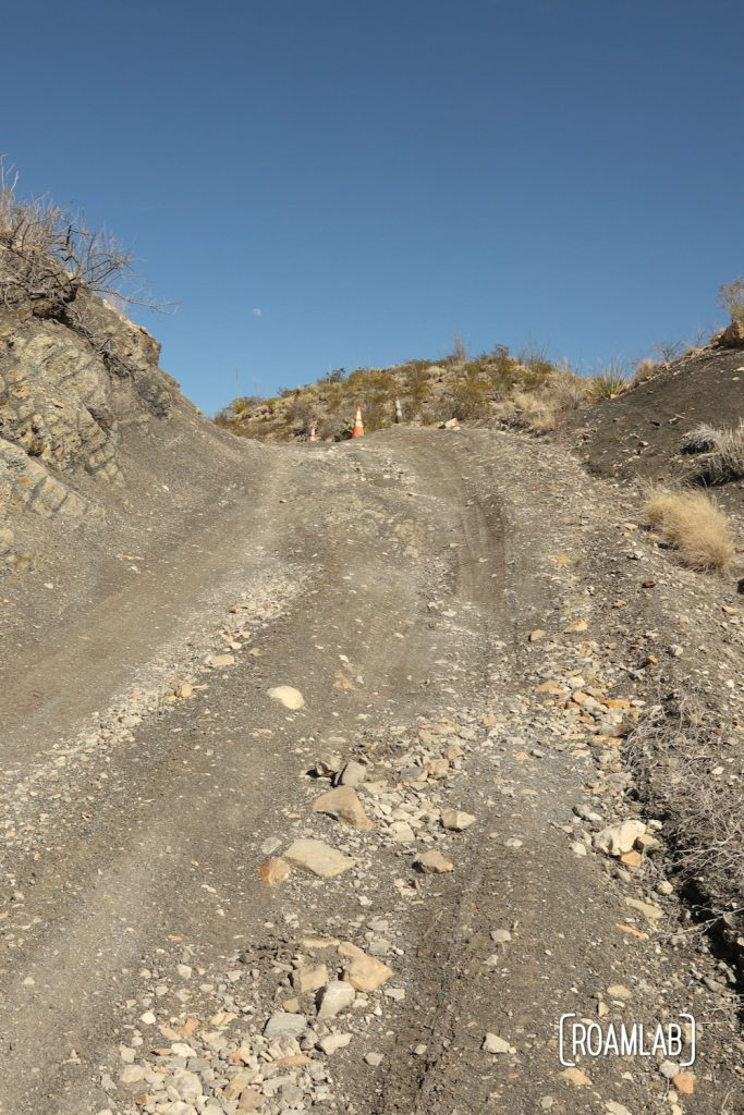 A steep rocky rutted road with a safety cone at the top and blue sky above along Old Ore Road in Big Bend National Park, Texas.
