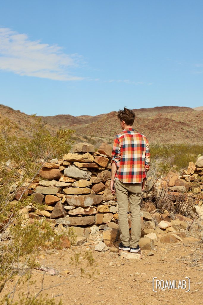 Man in a colorful plaid shirt standing next to stacked stone walls of a crumbling structure in the desert along Old Ore Road in Big Bend National Park, Texas.