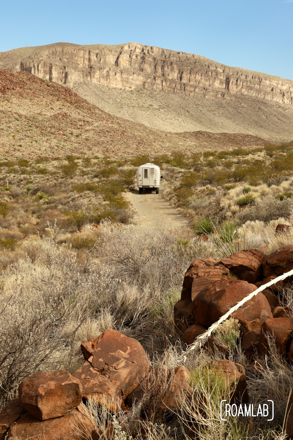 Dusty 1970 Avion C11 truck camper driving down a single land dirt road approaching the dramatic cliffs of the Alto Relex paralleling Old Ore Road in Big Bend National Park, Texas.