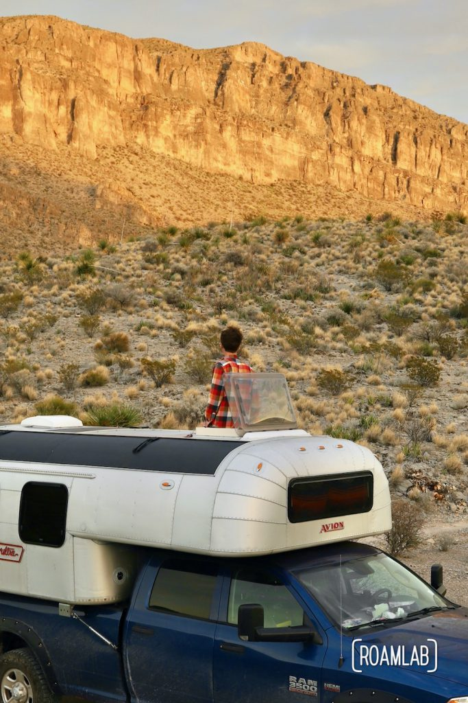 Man looking at golden cliffs through the roof hatch of a 1970 Avion C11 truck camper parked in the Telephone Canyon 1 campsite off of Old Ore Road in Big Bend National Park, Texas.