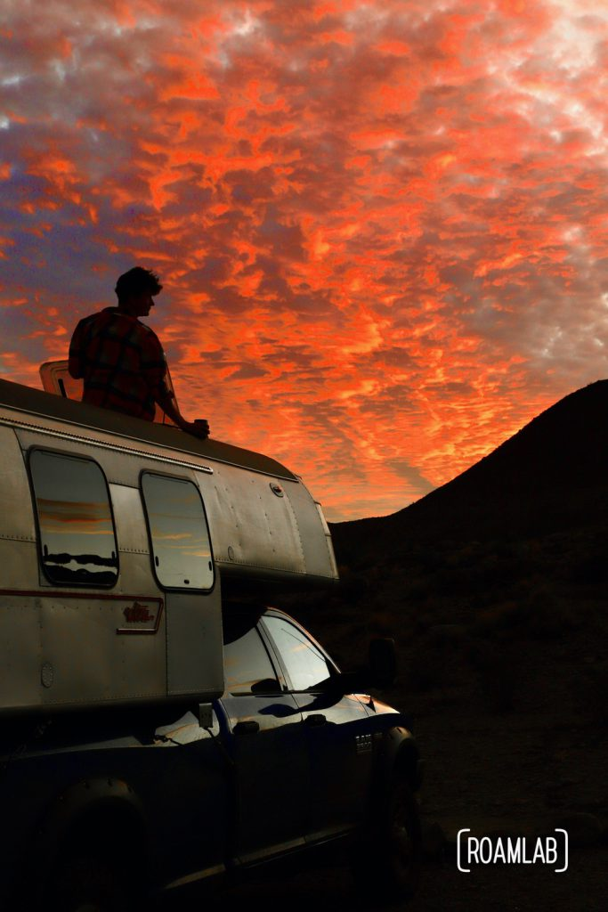 Brilliant red sunset lighting up the clouds silhouetting a man peaking out of a roof hatch of a 1970 Avion C11 truck camper parked at Telephone Canyon 1 campsite off of Old Ore Road in Big Bend National Park, Texas.