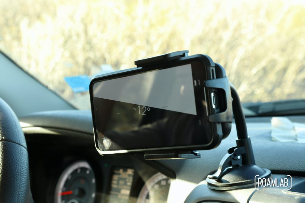 Cell phone mounted on a truck dashboard with a level app marking a -12% angle.