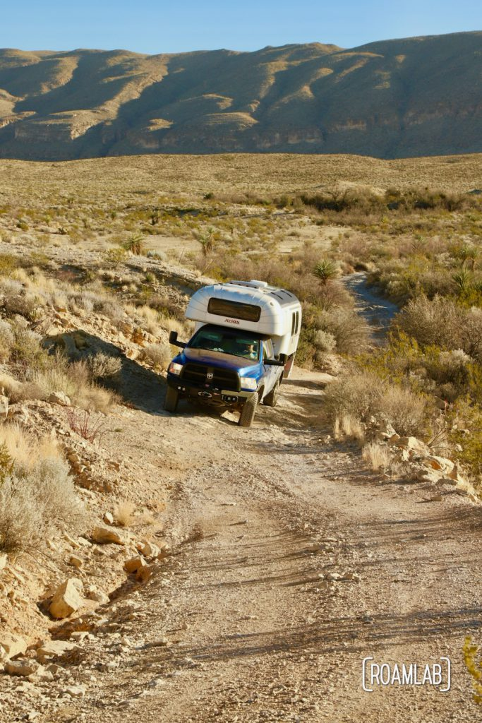 Aluminum 1970 Avion C11 truck camper on a blue Ram ascending the steep, uneven dirt Old Ore Road in Big Bend National Park, Texas