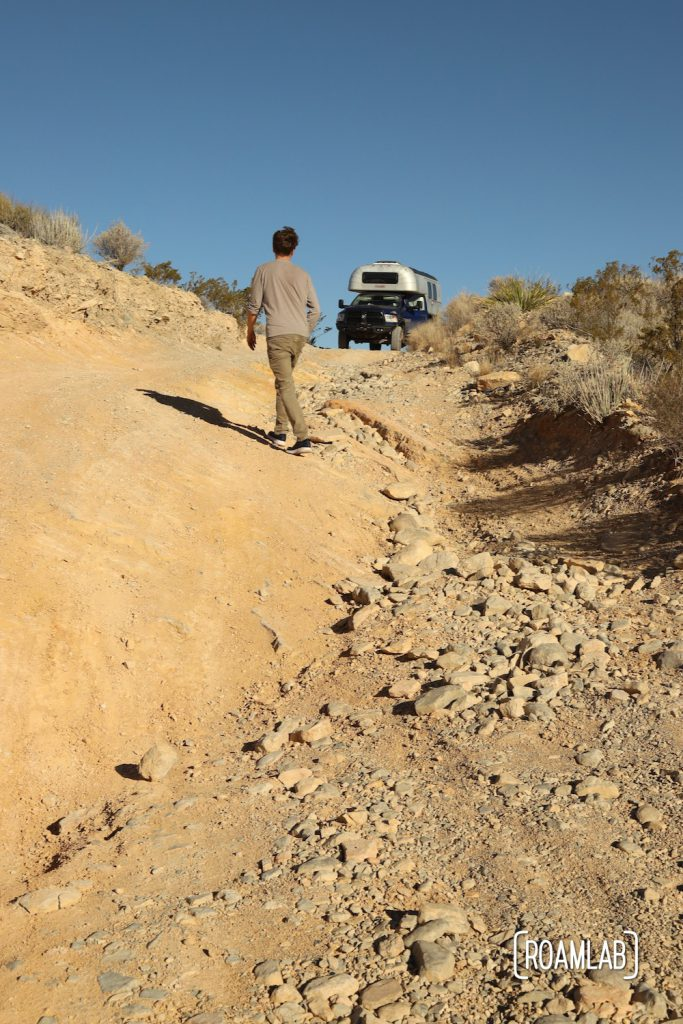 Man scouting the decent along a steep and rocky dirt road with a 1970 Avion C11 truck camper waiting along the Old Ore Road in Big Bend National Park, Texas