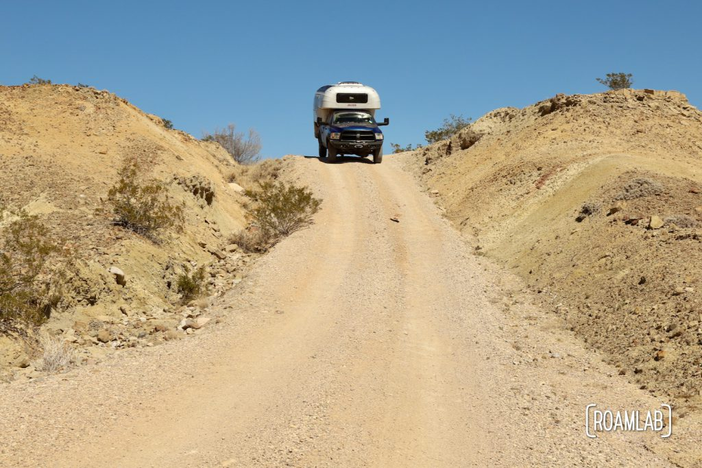 1970 Avion C11 truck camper at the top of a dirt washboard road down a hill