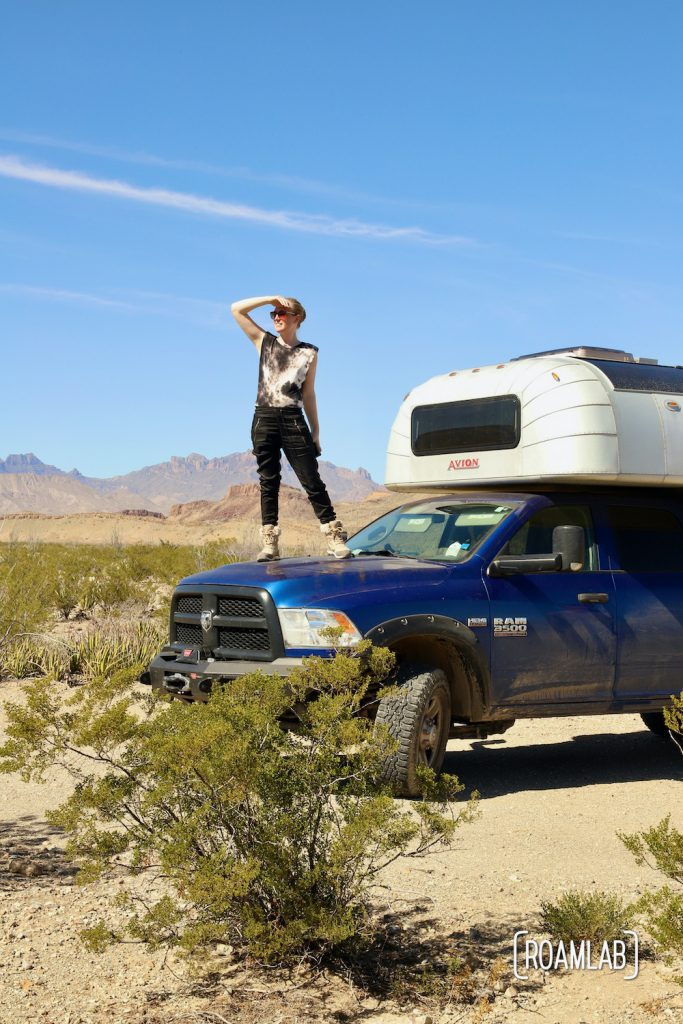 Woman standing on the hood of a 1970 Avion C11 truck camper parked at Fresno Campsite off River Road in Big Bend National Park, Texas.