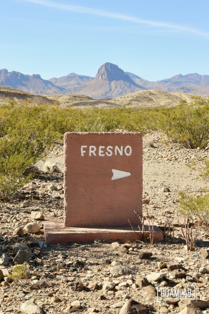 Pinkish stone marker pointing right to Fresno Campground, among rocky desert with shrub brush and mountains in the distance off River Road in Big Bend National Park, Texas.