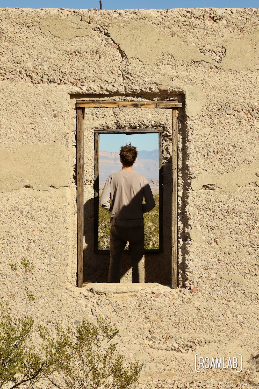 Man framed in the windows of an old stucco building.