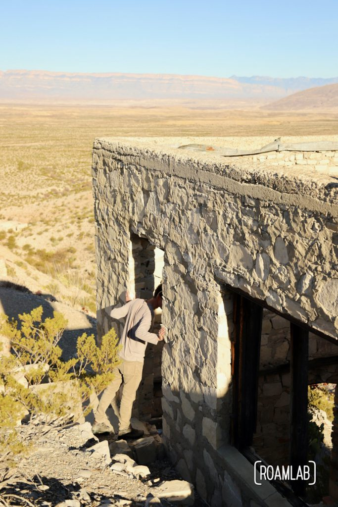 Man looking into a grey stone building with a desert spread out below.