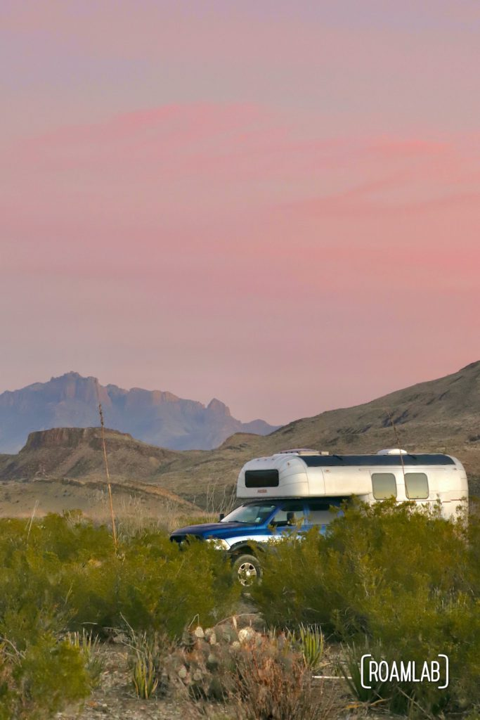 Pink sunrise skies over a 1970 Avion C11 truck camper with mountains in the background at Fresno Campsite off River Road in Big Bend National Park, Texas.