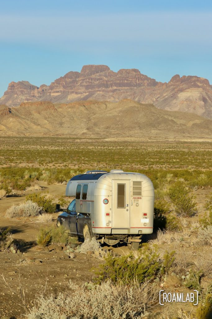 Golden 1970 Avion C11 trruck camper driving towards the Chisos Mountains in the Big Bend National Park in south west Texas.