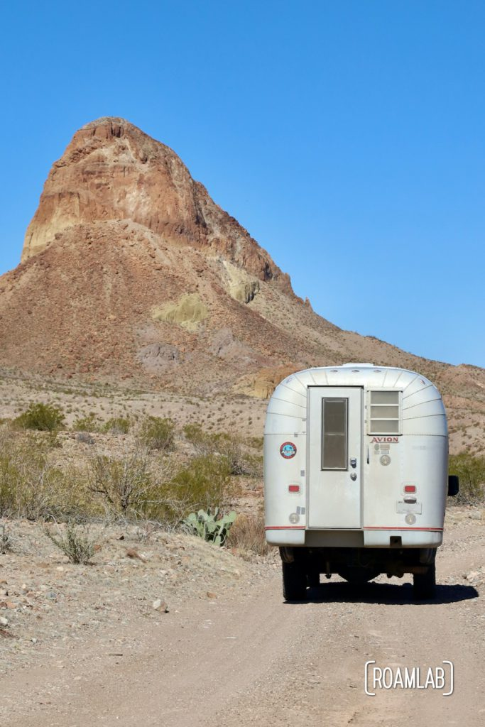 Silver 1970 Avion C11 truck camper on a dirt road with a large colorful bluff to the left at the western terminus of River Road in Big Bend National Park, Texas.