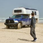 Man walking in front of a 1970 Avion C11 truck camper parked on the South Padre Island beach in Texas