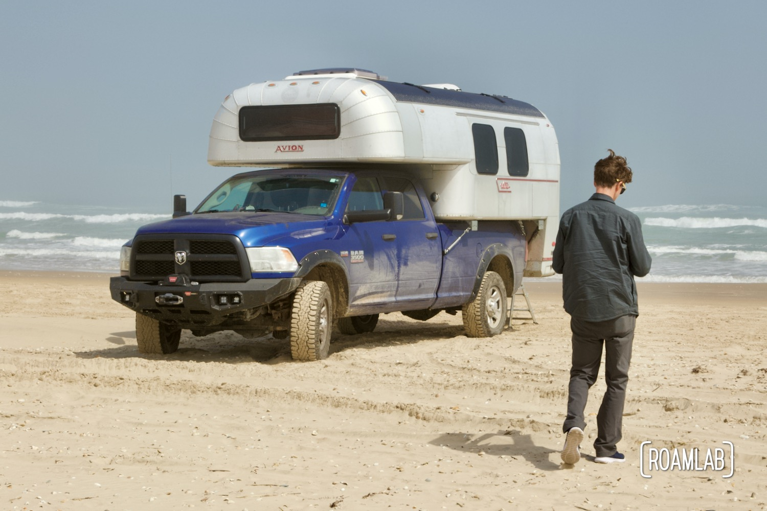 Man walking in front of a 1970 Avion C11 truck camper parked on the beach in South Padre Island, Texas