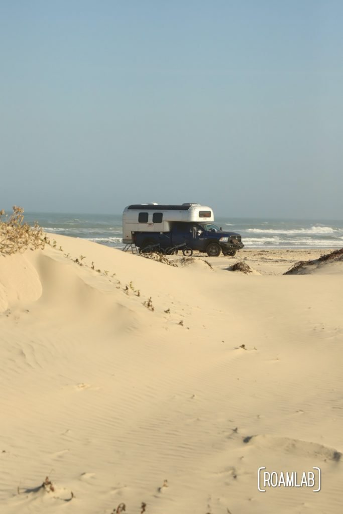 Vintage 1970 Avion C11 truck camper parked among the dunes in South Padre Island, Texas