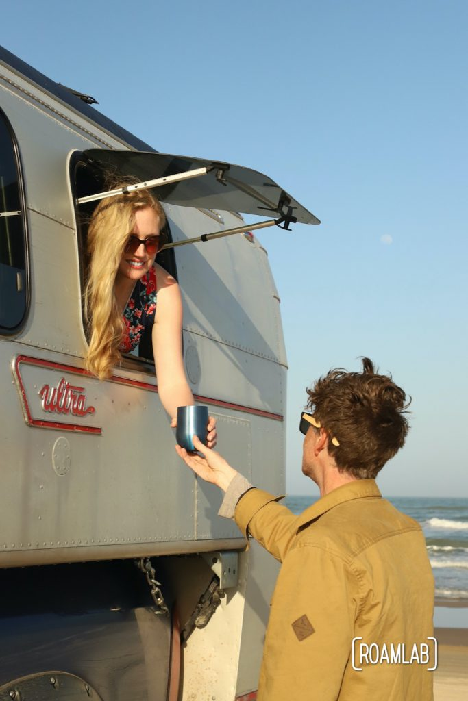 Woman in a 1970 Avion C11 truck camper passing a wine glass to a man standing on the beach with waves in the background in South Padre Island, Texas.