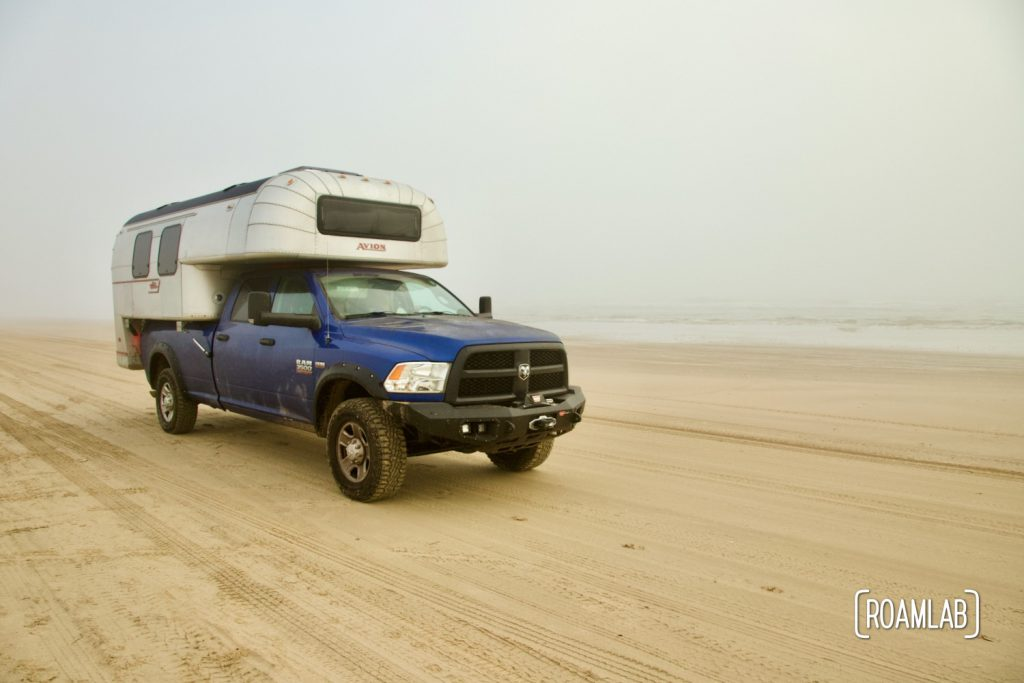 Vintage 1970 Avion C11 truck camper driving down the beach in South Padre Island, Texas