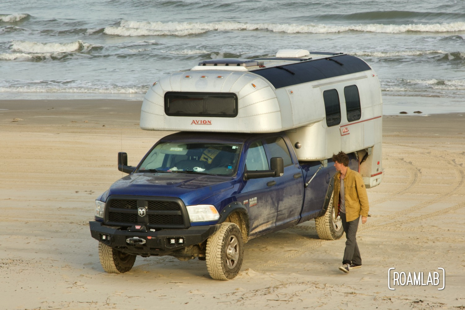 Man walking along the beach, inspecting a 1970 Avion C11 truck camper parked by the water at South Beach Padre Island National Seashore, Texas.