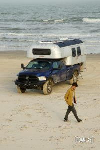 Man walking along the beach past at 1970 Avion C11 truck camper parked by the water at South Beach Padre Island National Seashore, Texas.