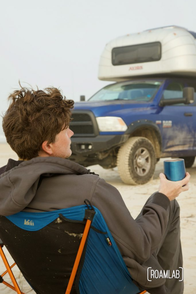 Man sitting in a collapsible camping chair on the beach, holding a blue glass in front of a 1970 Avion C11 truck camper at South Beach Padre Island National Seashore, Texas.