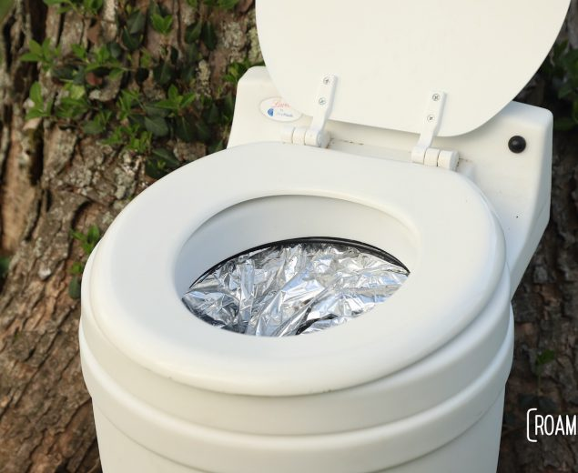 Laveo By Dry Flush toilet with cartridge installed, sitting in front of an ivy covered tree.