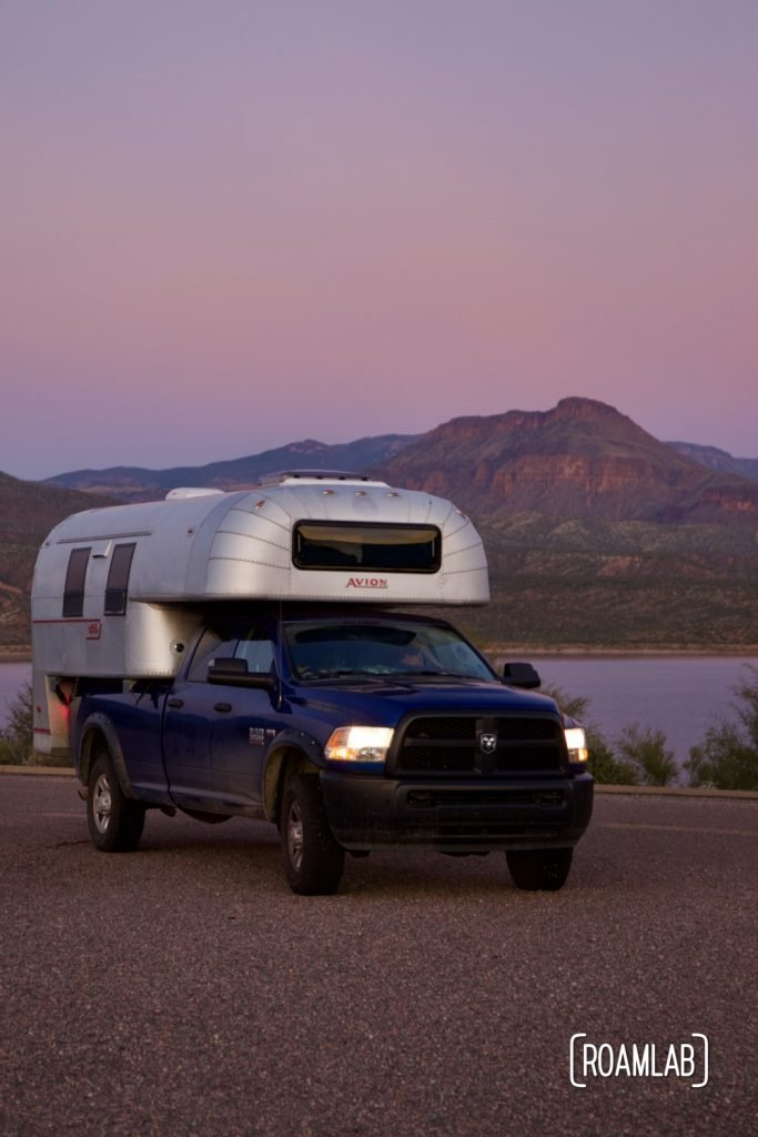 1970 Avion C11 truck camper parked at Cholla Campground with Roosevelt Lake in the background at sunset.