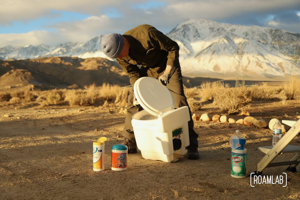 Man cleaning a dry flush toilet with the Sierra Nevada in the background.