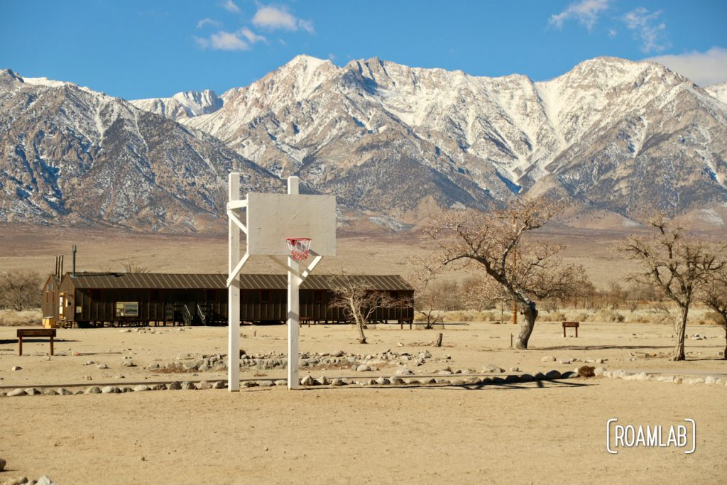 White plywood basket ball hoop over a dirt court with brown barracks in the background and snow capped mountains in the background of Manzanar National Historic Site.