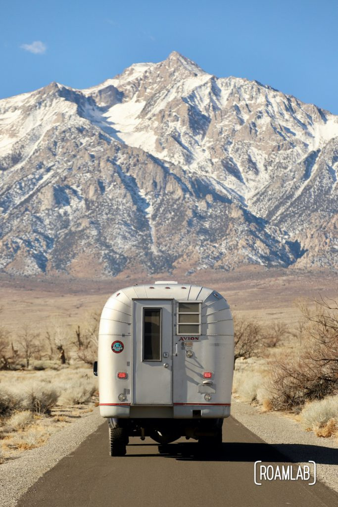 Rear view of a 1970 Avion C11 truck camper driving toward a snow capped mountain in the Sierra Nevada.