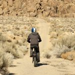 Man biking down a rough sandy trail toward a pile of boulders in the Alabama Hills.