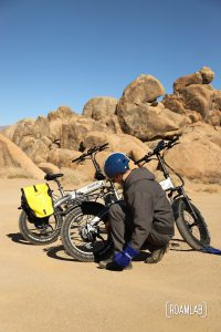 Man crouching next to bikes, looking at the tires, with golden boulders and a clear blue sky.