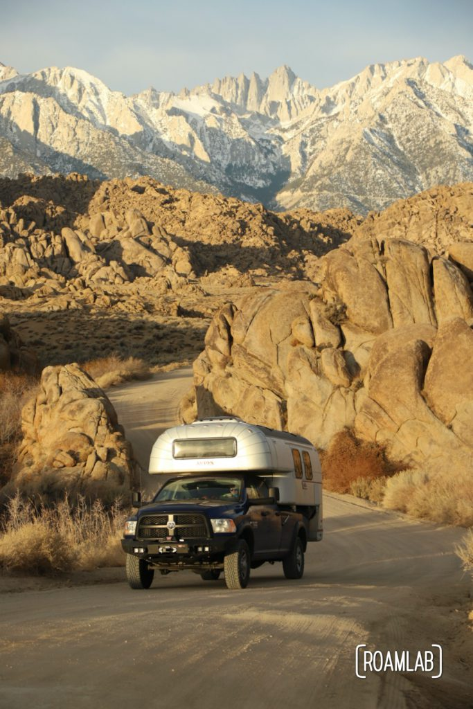 1970 Avion C11 truck campere driving up a winding stretch of Movie Road in the Alabama Hills with Mount Whitney in the background.