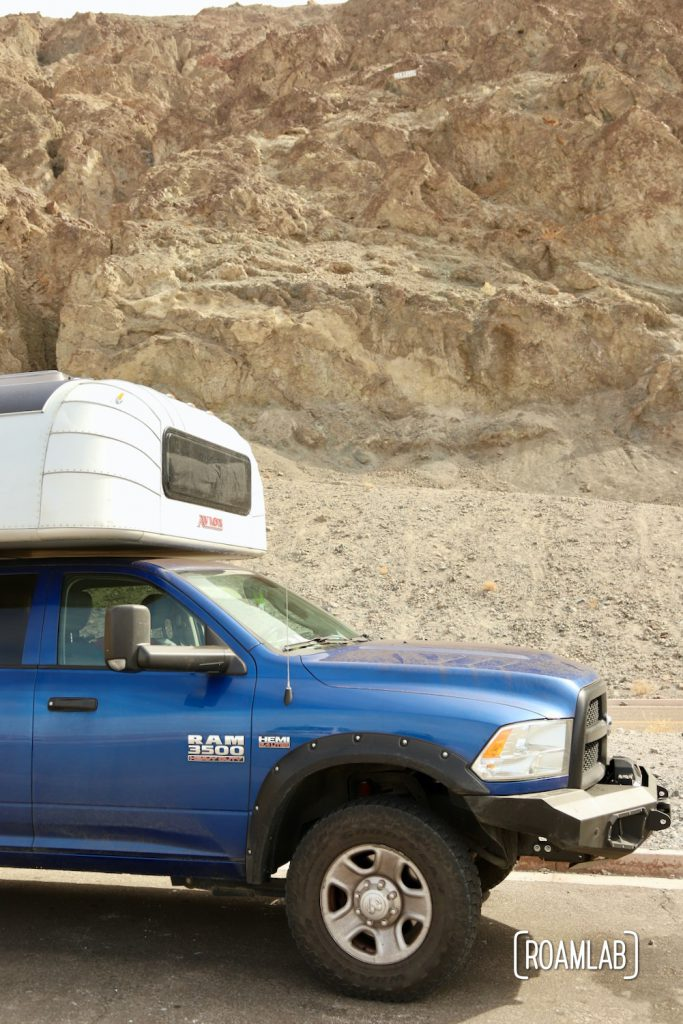 """Blue truck and silver aluminum camper parked next to a tan cliff with a """"sea level"""" marker hundreds of feet above"""