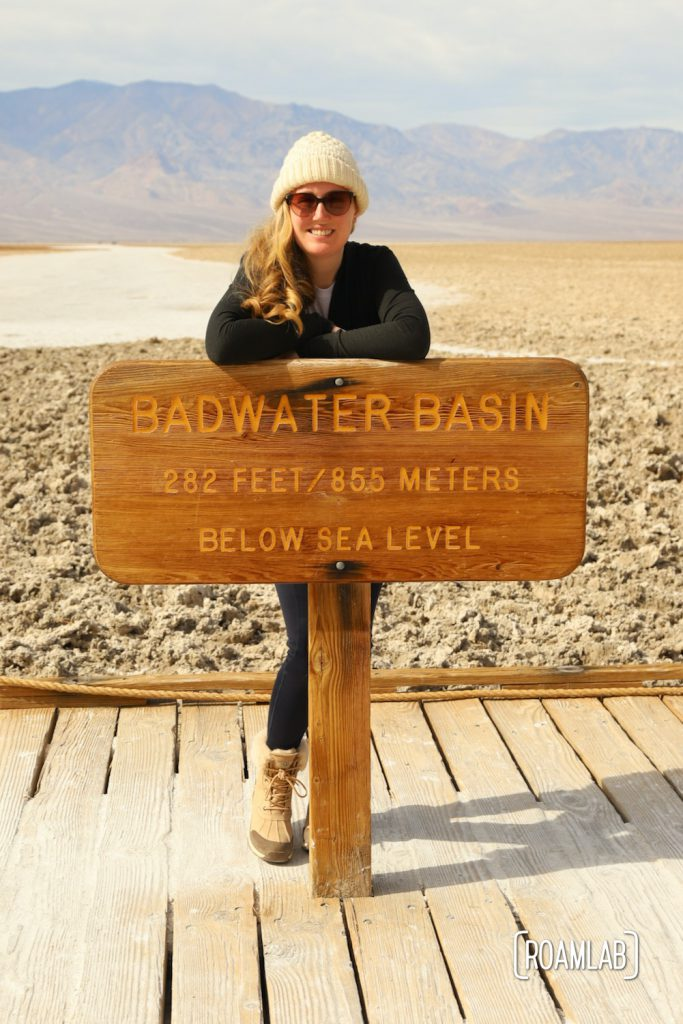 Woman standing behind sign for Badwater Basin.