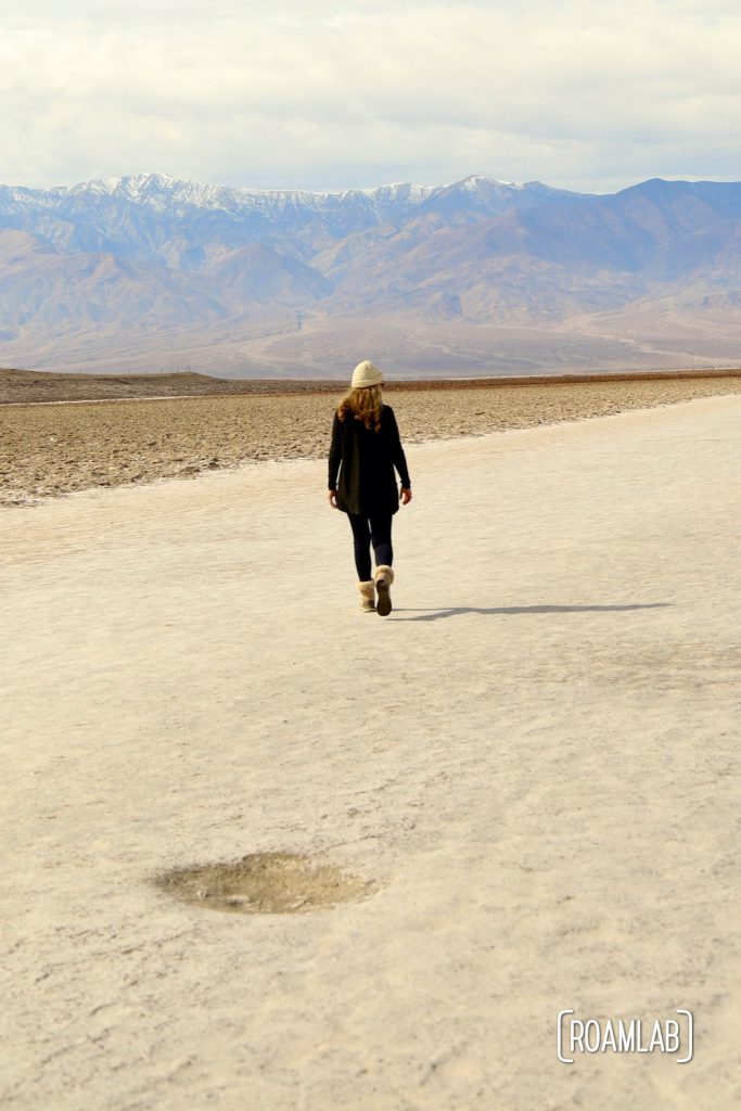 Woman in black walking out on a wide sandy trail of a dry lake bed in Death Valley's Badwater Basin.