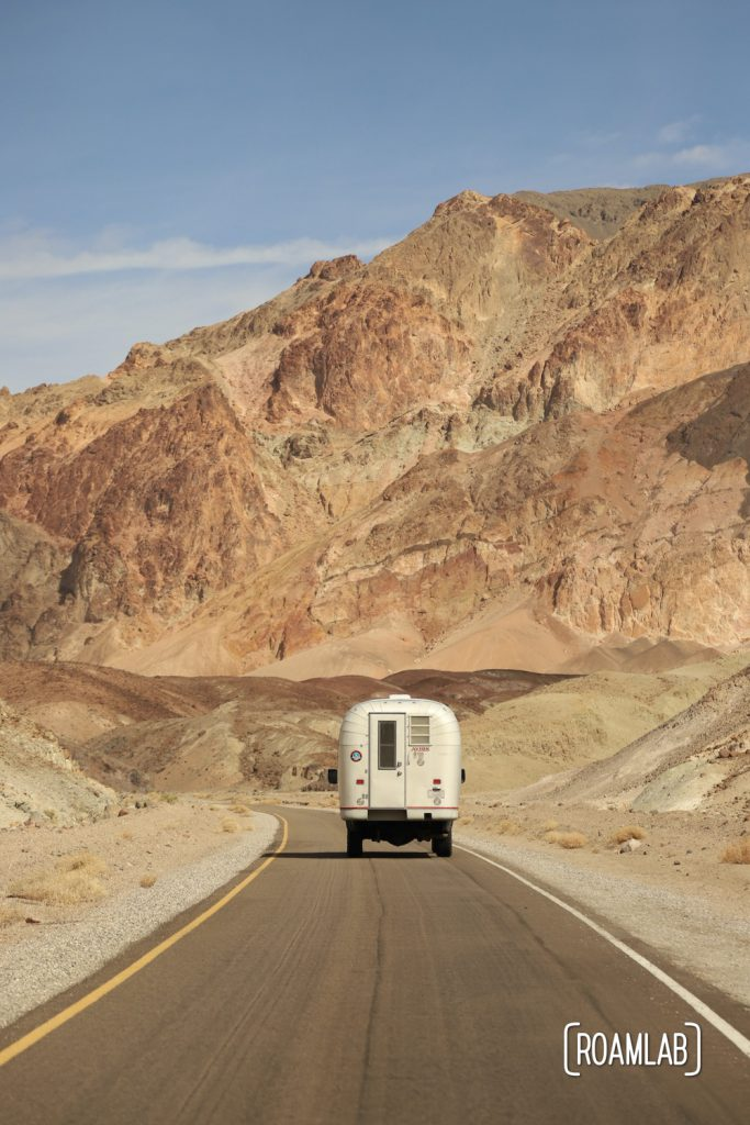 1970 Avion C11 truck camper driving down Artists Dive Scenic Loop in Death Valley National Park